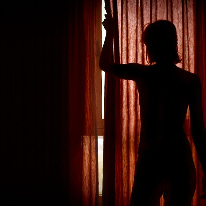 Silhouette behind closed red curtains
