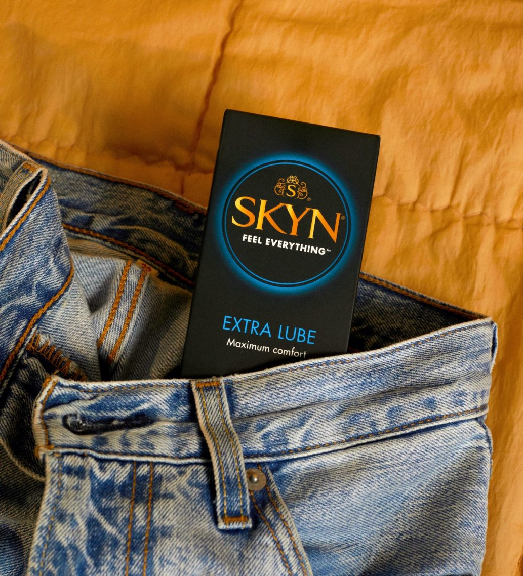 SKYN Extra Lube condom box inside a pair of blue jeans