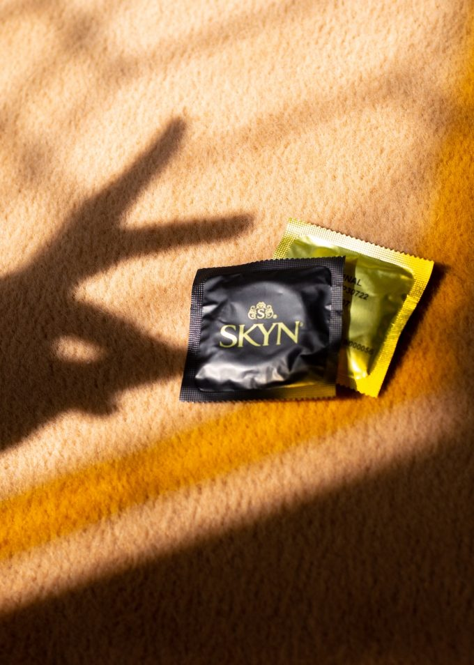 Hand shadow over two SKYN condom sleeves