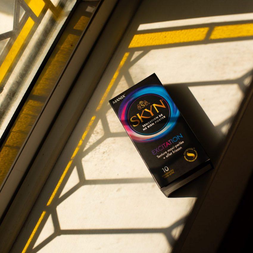 SKYN Excitation condom box under a window