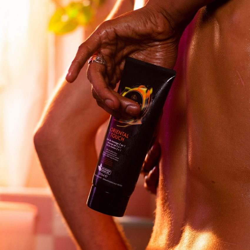 Bare back of a girl, man hand holding a SKYN Oriental Touch Lubricant