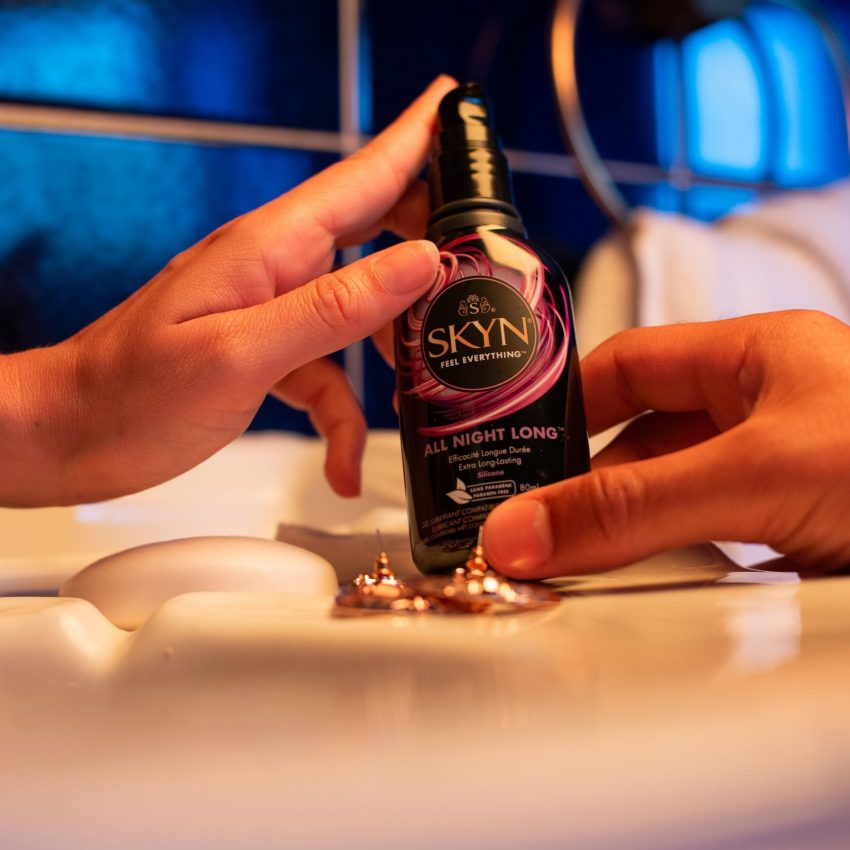 Boy and girl hands holding a SKYN All Night Long lubricant