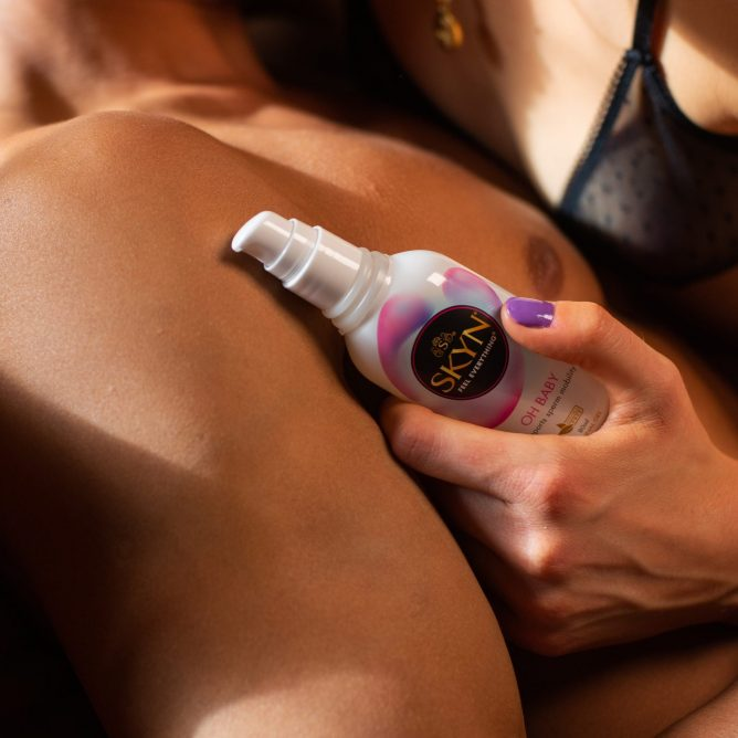 Girl holding a SKYN Oh Baby lubricant