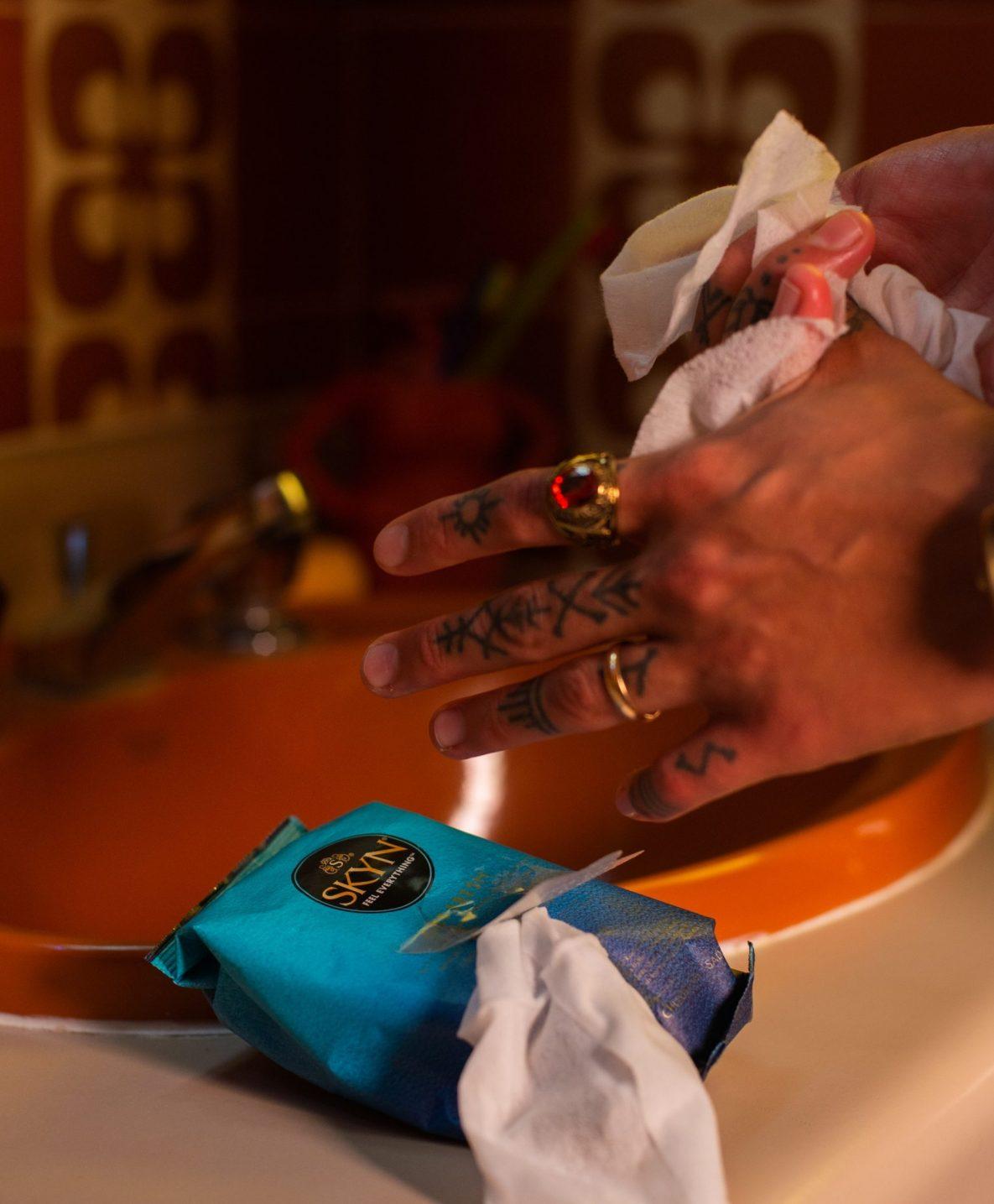Tattooed hands cleaned by a SKYN Get Fresh wipe