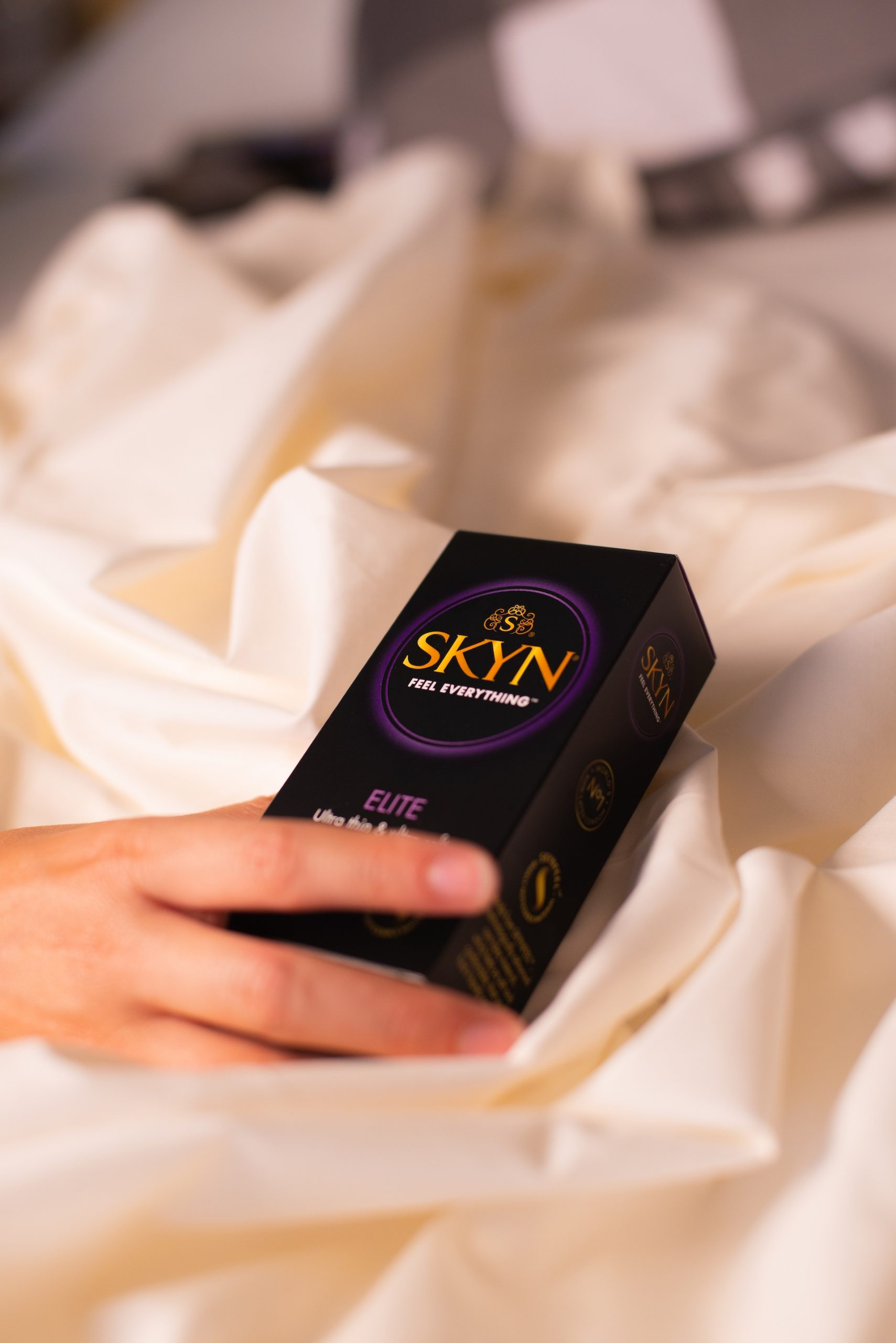 Hand reaching over a SKYN Elite condom box