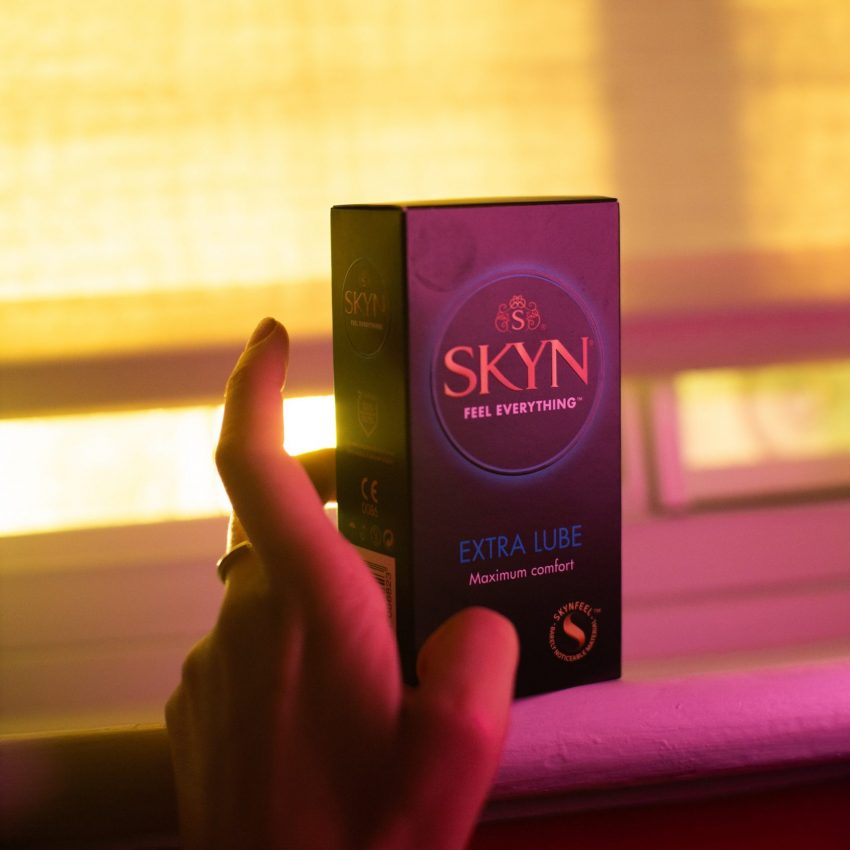 Hand holding SKYN Extra Lube condom box