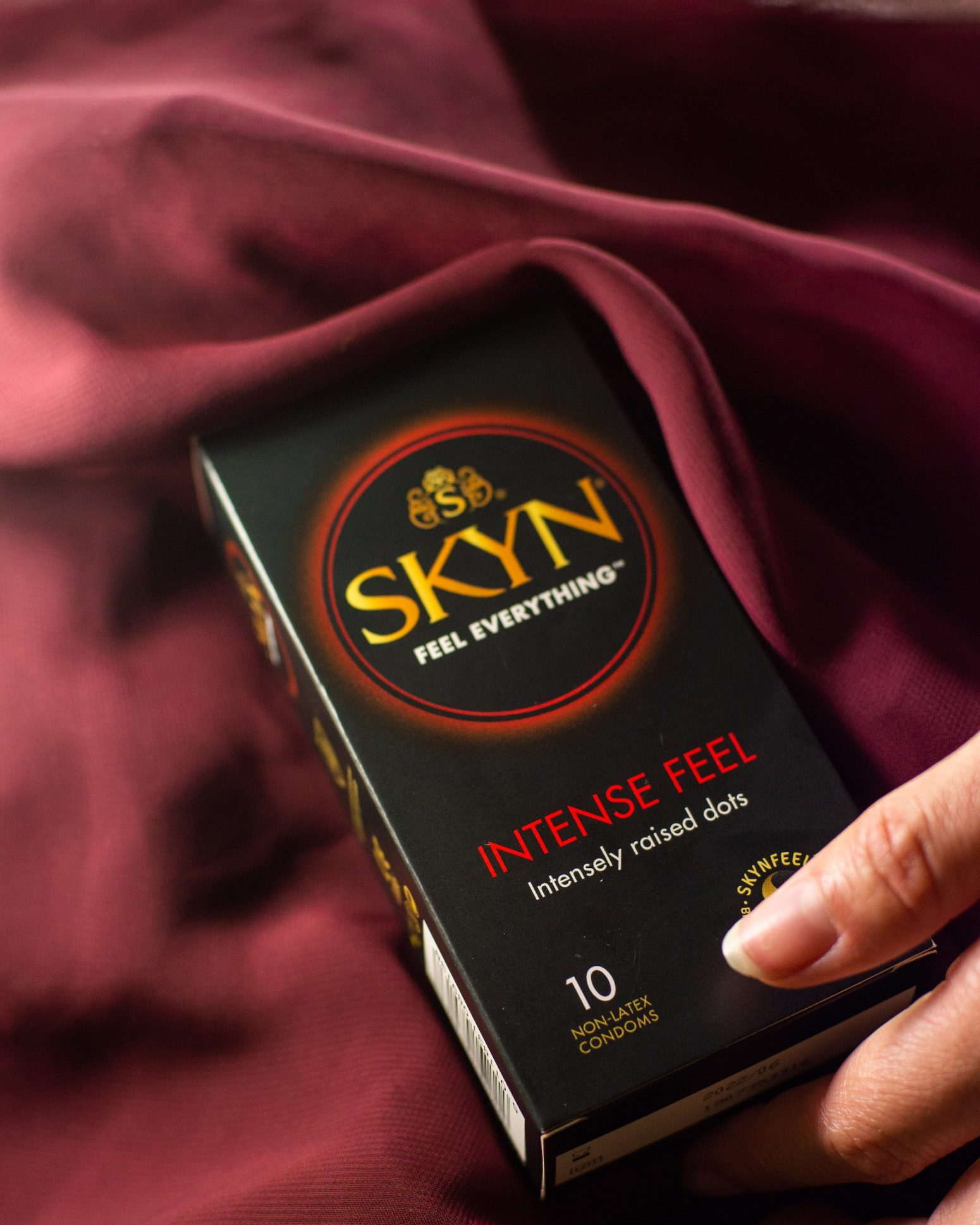 Hand reaching SKYN Intense Feel condom box