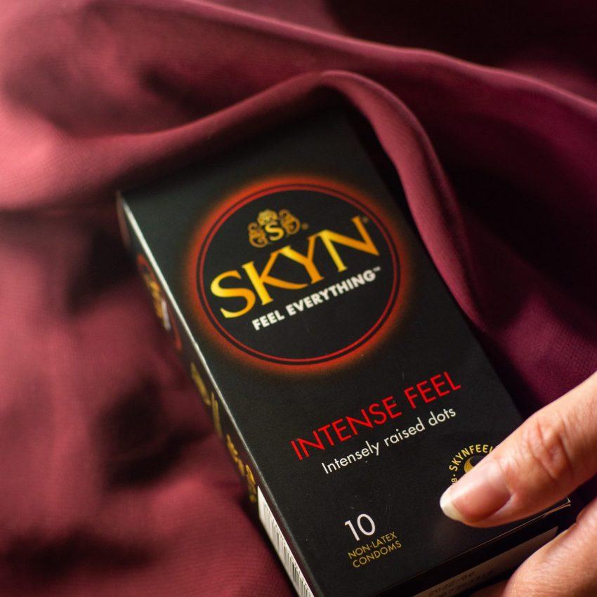 Hand reaching SKYN Intense Feel condom box